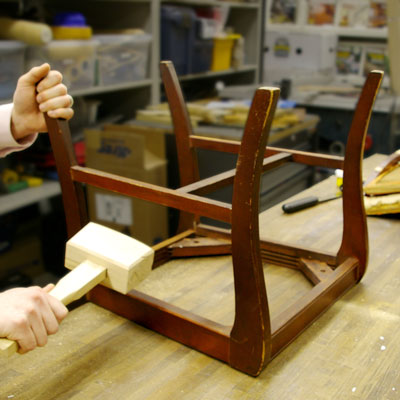 separating the joints near a dining chair's seat corner with a wooden mallet