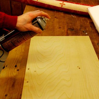 spraying the plywood seat bottom with spray adhesive