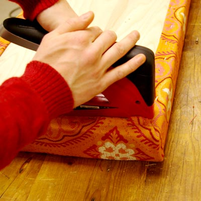 attaching upholstery fabric to the garden bench seat with a staple gun