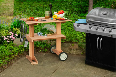 outdoor rolling grill table with grill nearby on patio
