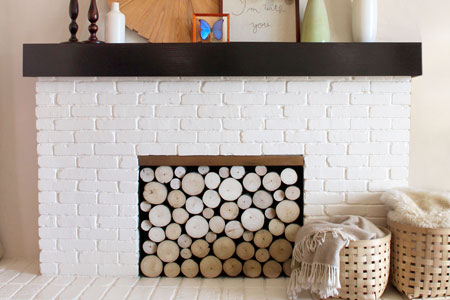 painted white brick fireplace with stacked log imitation summer front