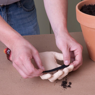 using velcro tape to attach vintage gardening hand tool to hand for halloween zombie hand planters