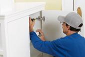 man installing euro style hinges inside cabinet