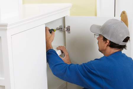 man installing euro style hinges inside cabinet