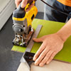 Mark Powers trims linoleum tiles with a miter saw