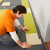 Mark Powers places a notched linoleum tile to fit the door casing