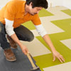 Mark Powers arranges the pattern for a course of linoleum tiles