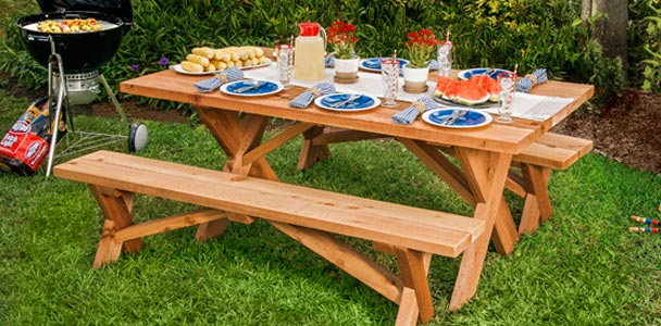 picnic table in a lush, green yard with a round charcoal grill off to one side with cooking kabobs, and the table is set for six in blue and white, and there is a platter of corn, cut watermelon, and a jug of lemondade