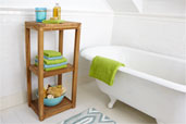 Three-Tier Towel Shelf in solid plantation-grown teak set against white subway tile next to a claw foot rug, with a bowl of sponges on the lower shelf, and small towels and washcloths on the middle shelf, and bath oil, soap, washcloth, and candle on top