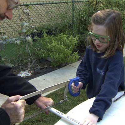Slater Harrison and little girl cutting PVC with hacksaw