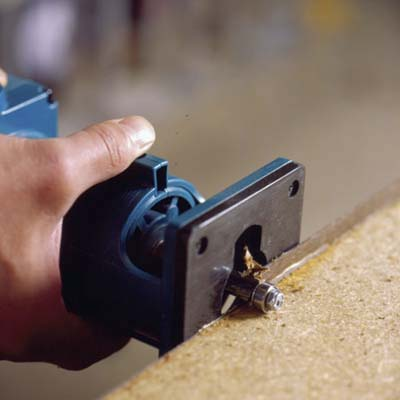 using the router turned on its side, cut off the overhanging edges of laminate, running the bit counterclockwise around the edges