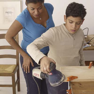 family sands the pieces of wood for building step stool
