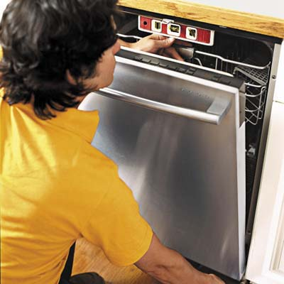 man fixing the dishwasher under the cabinet