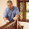 man waxing and buffing the wooden stair rail with furniture wax