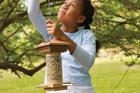 girl hanging handmade bird feeder