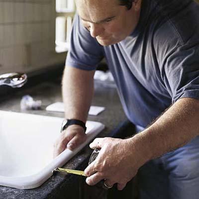 Richard Trethewey setting a kitchen sink