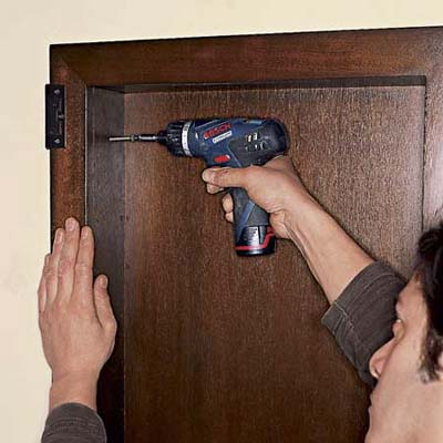 Drive drywall screws through the holes in the side of the cabinet and into the blocking
