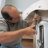 Richard Trethewey connecting the drain of a pedestal sink