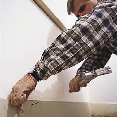 Tom Silva installing baseboard
