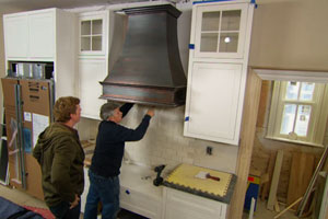 Tom Silva and Kevin O'Connor oversee installation of a vent hood in Arlington