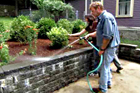 Roger Cook watering newly planted shrubs above a retaining wall with homeowner behind him