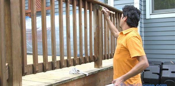 this old house senior technical editor mark powers using a paint brush on a deck rail and  balusters in how to refresh a deck