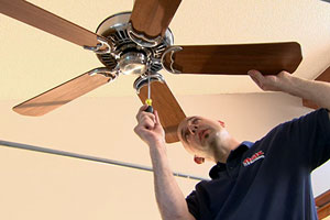 electrician Scott Caron installs a fan on a cathedral ceiling