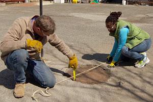 Roger Cook teaches a homeowner how to fill a pothole in an asphalt driveway