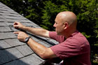 Scott Caron helps a homeowner install heat cables on his roof to stop ice dams