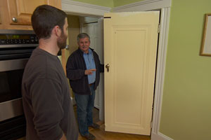 Tom Silva helps a homeowner to hang an interior door