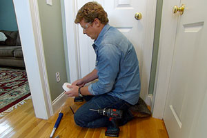 Kevin O'Connor helps a homeowner install a wireless alarm system